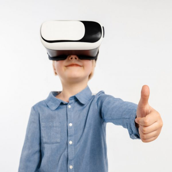 Coolest emotions. Little girl or child in jeans and shirt with virtual reality headset glasses isolated on white studio background. Concept of cutting edge technology, video games, innovation.