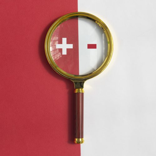 Plus and minus signs through magnifying glass on red and white background. Concept of positive and negative, pros and cons compare.